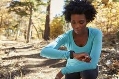 Молодая чернокожая женщина вставать в лесе проверяя smartwatch стоковые фотографии rf