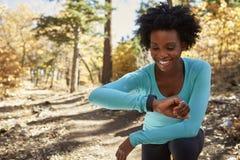 Молодая чернокожая женщина в лесе проверяя smartwatch и усмехаться стоковое изображение rf