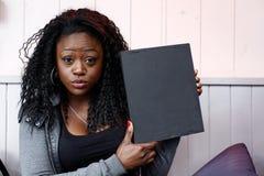 Молодая чернокожая женщина держа малую черную доску Стоковое Изображение RF