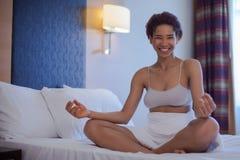Молодая чернокожая женщина делая йогу дома в положении лотоса Стоковое Изображение