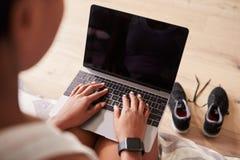 Молодая чернокожая женщина используя портативный компьютер, взгляд сверх-плеча стоковое фото rf