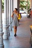 Молодая чернокожая женщина идя с мобильным телефоном и хозяйственными сумками Стоковые Изображения RF