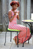 Молодая чернокожая женщина наслаждаясь кофе на патио Стоковая Фотография RF