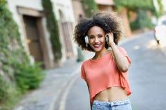 Молодая чернокожая женщина с афро стилем причёсок усмехаясь в городском парке Стоковые Фотографии RF