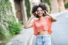 Молодая чернокожая женщина с афро стилем причёсок усмехаясь в городском парке Стоковое Изображение