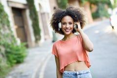 Молодая чернокожая женщина с афро стилем причёсок усмехаясь в городском парке Стоковые Изображения RF
