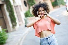Молодая чернокожая женщина с афро стилем причёсок усмехаясь в городском парке Стоковое фото RF