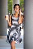 Молодая чернокожая женщина усмехаясь и держа мобильный телефон Стоковое Фото