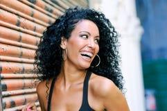 Молодая чернокожая женщина усмехаясь с расчалками Стоковое фото RF