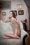 Молодая чувственная женщина сидя на софе ослабляя Красивая длинная девушка волос с удобными одеждами daydreaming на кресле, самос Стоковая Фотография