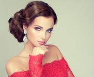 Молодая, шикарная модель одела в красной мантии стоковое фото rf