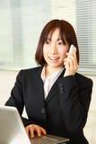 Молодая японская бизнес-леди разговаривает с умным телефоном Стоковые Фотографии RF