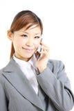 Молодая японская коммерсантка говоря на умном телефоне Стоковое Изображение RF