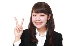 Молодая японская коммерсантка показывая знак победы Стоковые Фото