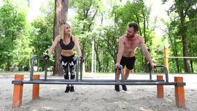 Молодая sportive женщина и бородатый делать человека нажим-поднимают тренировки в parrk сток-видео