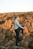 Молодая sportive тренировка девушки, sctretching на утесе в каньоне Стоковые Фото