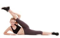 Молодая sporty девушка делая протягивающ изолированную тренировку Здоровый уклад жизни Стоковая Фотография RF