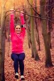 Молодая sporty девушка делая тренировки в лесе Стоковые Фотографии RF