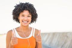 Молодая sporty женщина наслаждаясь музыкой и делая большие пальцы руки вверх стоковое фото rf
