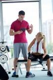Молодая sporty женщина с поднятием тяжестей тренировки тренера Стоковое Изображение