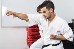 2 молодого человека в кимоно воюя во время их тренировки Стоковое Изображение RF