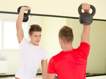 2 молодого человека в спортзале разрабатывая с kettlebells Стоковые Изображения