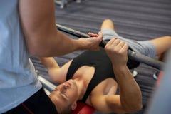 2 молодого человека при штанга изгибая мышцы в спортзале Стоковое Изображение RF