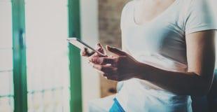 Молодое азиатское время остатков траты женщины дома на солнечном воскресенье и smartphone удерживания на руках Запачканная предпо Стоковая Фотография RF