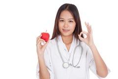 Молодое азиатское женское О'КЕЙ выставки доктора с яблоком Стоковые Изображения RF