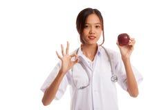 Молодое азиатское женское О'КЕЙ выставки доктора с яблоком Стоковая Фотография RF