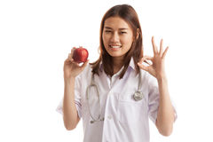 Молодое азиатское женское О'КЕЙ выставки доктора с яблоком Стоковые Изображения
