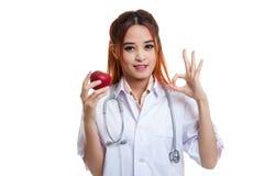 Молодое азиатское женское О'КЕЙ выставки доктора с яблоком Стоковая Фотография