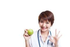 Молодое азиатское женское О'КЕЙ выставки доктора с яблоком Стоковое Изображение