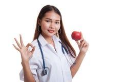 Молодое азиатское женское О'КЕЙ выставки доктора с яблоком Стоковое Фото