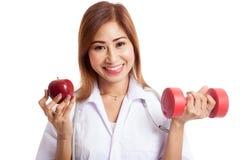 Молодое азиатское женское яблоко и гантель владением доктора Стоковая Фотография