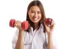 Молодое азиатское женское яблоко и гантель владением доктора Стоковое Изображение