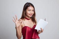 Молодое азиатское О'КЕЙ выставки женщины с книгой Стоковые Изображения