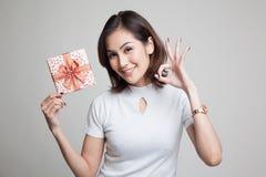 Молодое азиатское О'КЕЙ выставки женщины с подарочной коробкой Стоковые Фото