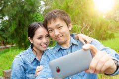 Молодое азиатское selfie взятия пар в парке Стоковые Фотографии RF