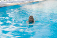 Молодое белокурое заплывание женщины в бассейне outdoors на зиме Стоковые Изображения