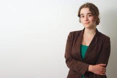 Молодое брюнет на белой предпосылке при коричневая рубашка держа ее руку Стоковое фото RF