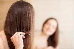 Молодое брюнет расчесывая ее волосы стоковые изображения rf