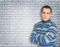 Молодое брюнет стоя против стены при пересеченные оружия стоковые фотографии rf