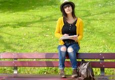 Молодое брюнет girlsitting на стенде с таблеткой в парке Стоковая Фотография RF