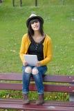 Молодое брюнет girlsitting на стенде с таблеткой в парке Стоковое Изображение