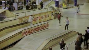 Молодое выскальзывание конькобежца ролика на загородке, делает эффектные выступления оператор смелости Конкуренция в skatepark сток-видео