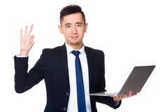 Молодое владение бизнесмена с портативным компьютером и одобренный знак показывать Стоковое Фото