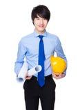 Молодое владение инженера с защитными шлемом и светокопией Стоковые Фото