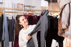 Молодое женское брюнет выбирая брюки стоковое изображение