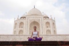 Молодое женское практикуя раздумье йоги на Тадж-Махале Стоковое Изображение